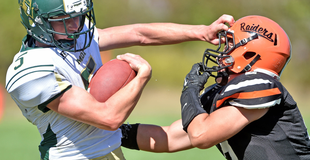 Staff photo by Michael G. Seamans   Winslow's Patrick Hopkins, right, defends Mount Desert Island's Colby Lee (5) on Saturday in Winslow.
