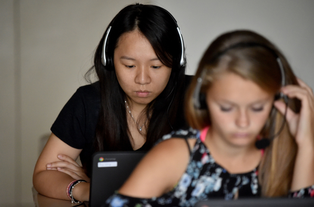 Paige Wong, 17, senior exchange student from Taiwan, back, works through Rosetta Stone lessons during Spanish language class at Madison Area Memorial High School on Sept. 8.