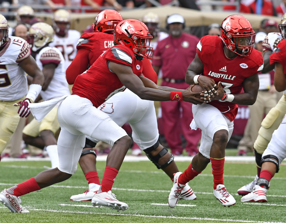 Louisville quarterback Lamar Jackson (8) fakes a handoff to Brandon Radcliff (23) during the first quarter against Florida State on Saturday in Louisville, Kentucky.