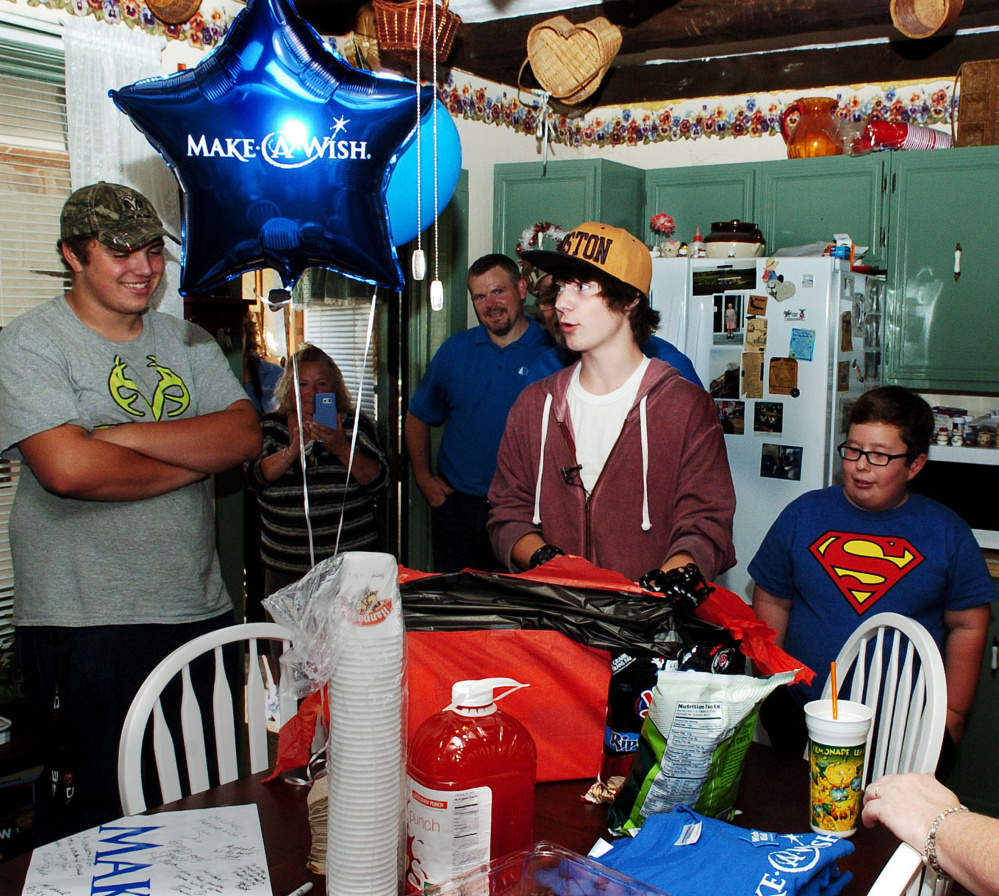 Michael Welcome, center, was the center of attention at a surprise party for him and the unveiling of his remodeled bedroom at his home in Madison on Tuesday. Welcome suffers from cystic fibrosis and received the new room through the Maine Make-A-Wish organization with help from Skowhegan Savings Bank.