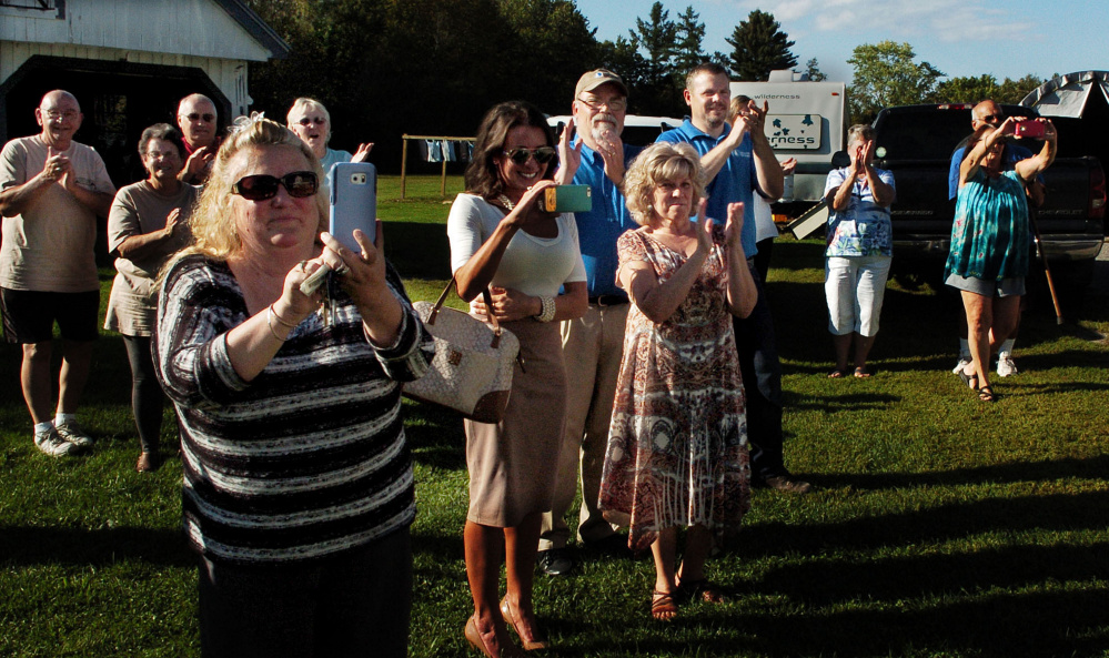 Friends, family and supporters take photos and clap as Michael Welcome arrives at his home in Madison in a limousine on Tuesday.