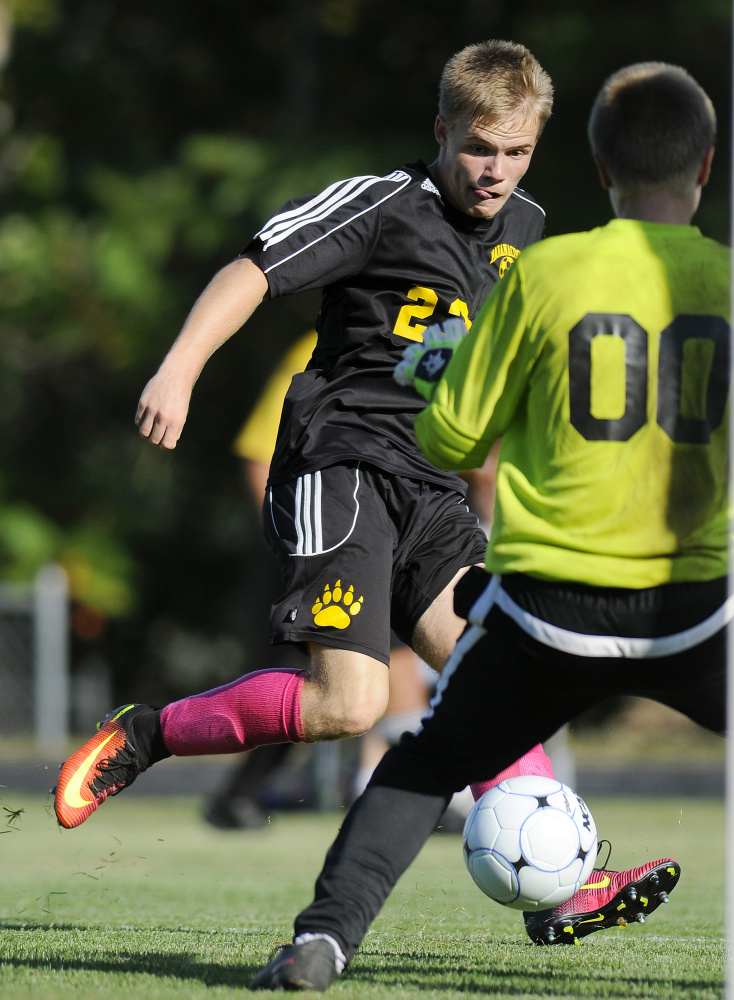 Maranacook senior striker Sam Wilkinson fires a shot past Erskine sophomore goalie David McGraw during a Class B game Tuesday in South China.