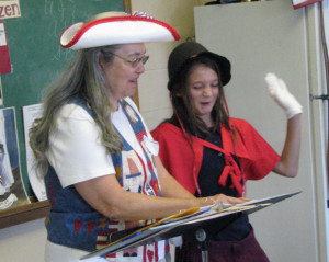 Sixth-grader Ava Nadeau, right, reads from the script with the Constitution Lady Bonnie Wilder during a Constitution Week celebration at St. Michael School in Augusta.