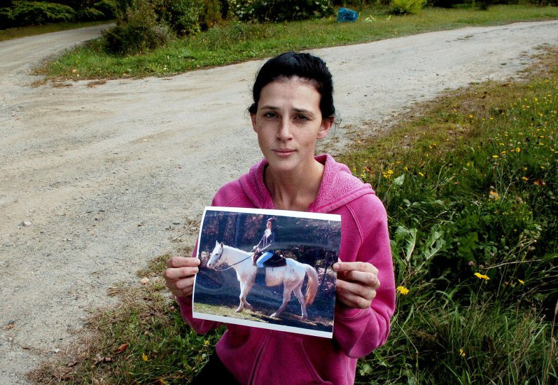 Sierra Miner holds a photograph of her 4-year-old mare, Lucy, last Thursday at the spot she said someone drove onto her property in Canaan a day earlier and struck and dragged the tethered horse to death. But police investigating the case say they haven't found any evidence a vehicle was involved in the horse's death.
