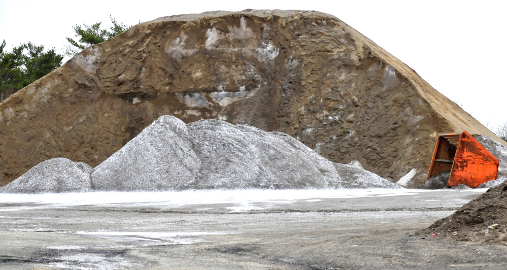 Light colored salt is stored beside a large pile of sand used for winter road work at the Winslow Public Works garage on April 12.