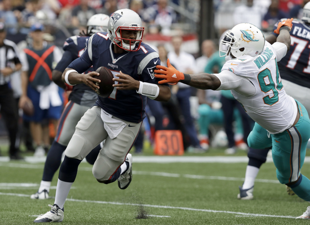 New England Patriots quarterback Jacoby Brissett (7) scrambles away from Miami Dolphins defensive end Mario Williams (94) during the second half Sunday in Foxborough, Massachusetts. Two months ago, Brissett was a third-string rookie. Tonight, he could become the first African-American quarterback to start a regular-season game for the New England Patriots.