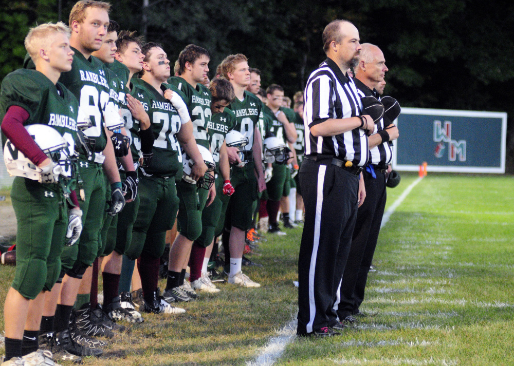Members of the Winthop/Monmouth football team and officials stand during the national anthem prior to a Campbell Conference Class D game against Dirigo last Friday at Maxwell Field in Winthrop.