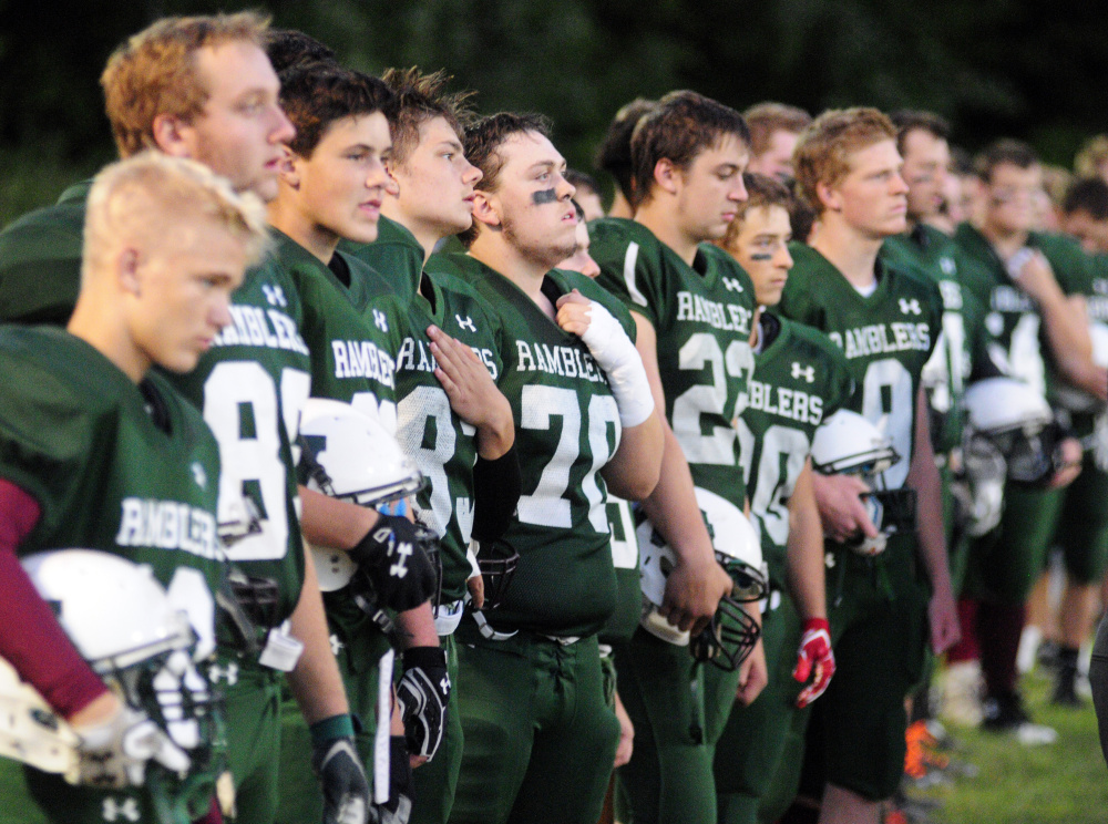 Members of the Winthop/Monmouth football team stand during the national anthem prior to a Campbell Conference Class D game against Dirigo last Friday at Maxwell Field in Winthrop.