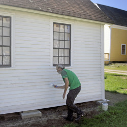 Colin McCabe paints the stencil shed at the Monmouth Museum in this Sept. 12, 2016 file photo. Volunteers are working diligently to prepare the structures and collections at the Museum for AppleFest on Saturday.