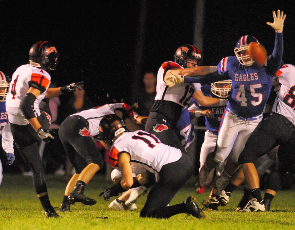Messalonskee's Yan Gusmanov, right, tries to block an extra point attempt by Brunswick's Aaron Carlton during a game Friday at Veterans Field in Oakland.