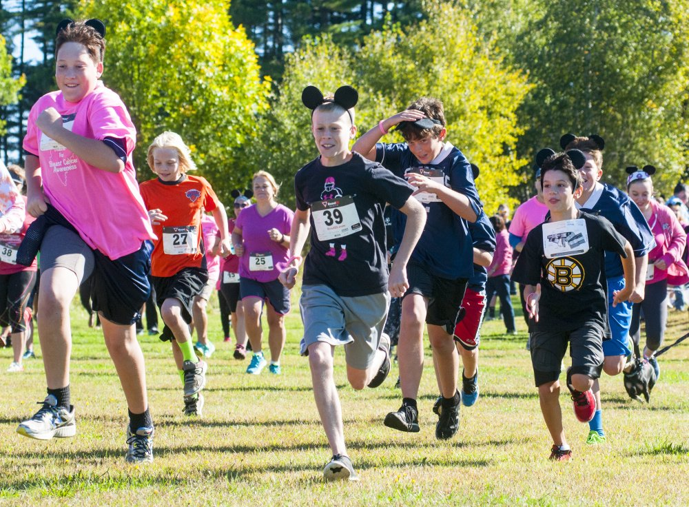 Participants, many wearing pink and mouse ears, sprint off from the starting line at the Miles Across Maine for Breast Cancer Awareness on Saturday at University of Maine of Augusta.