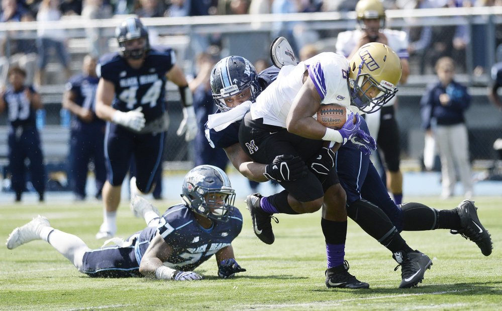 Maine defenders DeAndre Scott, left and Darius Greene, center, try and take down John Miller of James Madison during the first half Saturday in Orono.