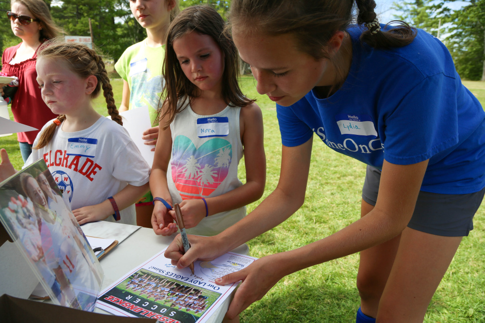 Messalonskee High School girls soccer player Lydia D'Amico, right, autographs a team poster for Nora Kalback, center, while Emmy Dunbar, left, waits her turn at Shine On Saturday Sept. 10 in Oakland.