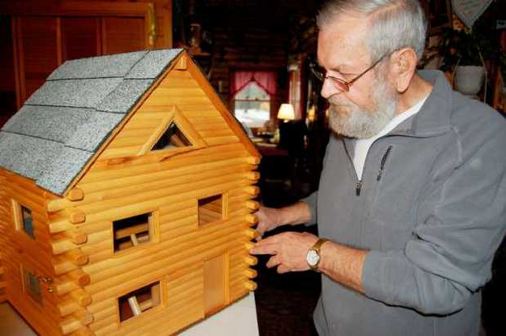 Lenny Ellis of New Vineyard unlocks the front one of his one-of-a-kind   toy log homes he builds out of wooden dowels. He is hoping to find a   way to give one of his creations to President Barack Obama's daughters.
