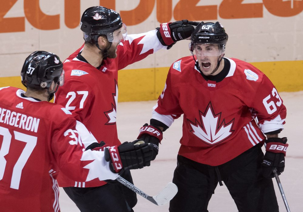 Team Canada center Brad Marchand (63) celebrates his game tying goal on Russia with teammates Alex Pietrangelo (27) and Patrice Bergeron (37)  during the second period of a World Cup of Hockey semifinal Saturday in Toronto.