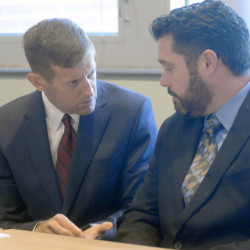 Bryan Carrier, right, and his attorney, Walt McKee, confer Monday during a hearing at the Bureau of Motor Vehicles in Augusta, where Carrier asked to have his driver'-s license restored.