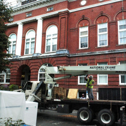 Workers on top of Waterville City Hall wait for others with Roofing Systems of Maine to use a crane to lift materials while replacing the building's roof Tuesday.