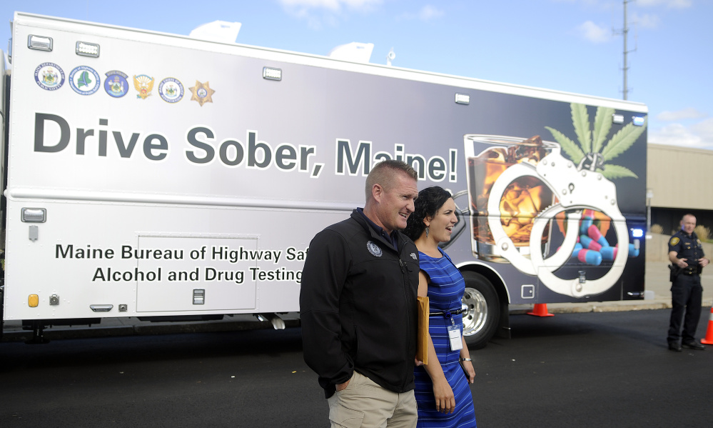 Form left, Augusta police Maj. Jared Mills,  Bureau of Highway Safety analyst Jessica Voisine and Augusta police Lt. Kevin Lully walk on Wednesday around the state's new impaired driving roadside testing vehicle, which was unveiled at the Maine Department of Public Safety in Augusta. The vehicle, which enables police to conduct sobriety tests on the road, was purchased with federal grant money for just under $300,000.