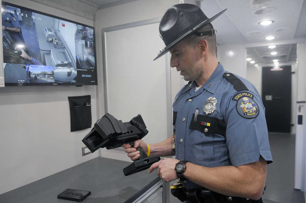 Maine State Police Trooper Aaron Turcotte inspects the DAX Evidence Recorder that is part of the state's new impaired driving roadside testing vehicle, which was unveiled Wednesday at the Maine Department of Public Safety in Augusta. The device records eye movements as evidence for police officers conducting field sobriety tests.