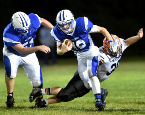 Madison quarterback Evan Bess evades Winslow defender Kenny Rickard during a Big Ten Conference game Friday night in Madison. The Bulldogs sank the Black Raiders to take control of the conference.