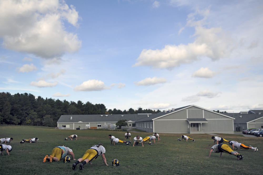 Members of the Maranacook football squad do push-ups during practice Tuesday in Readfield.