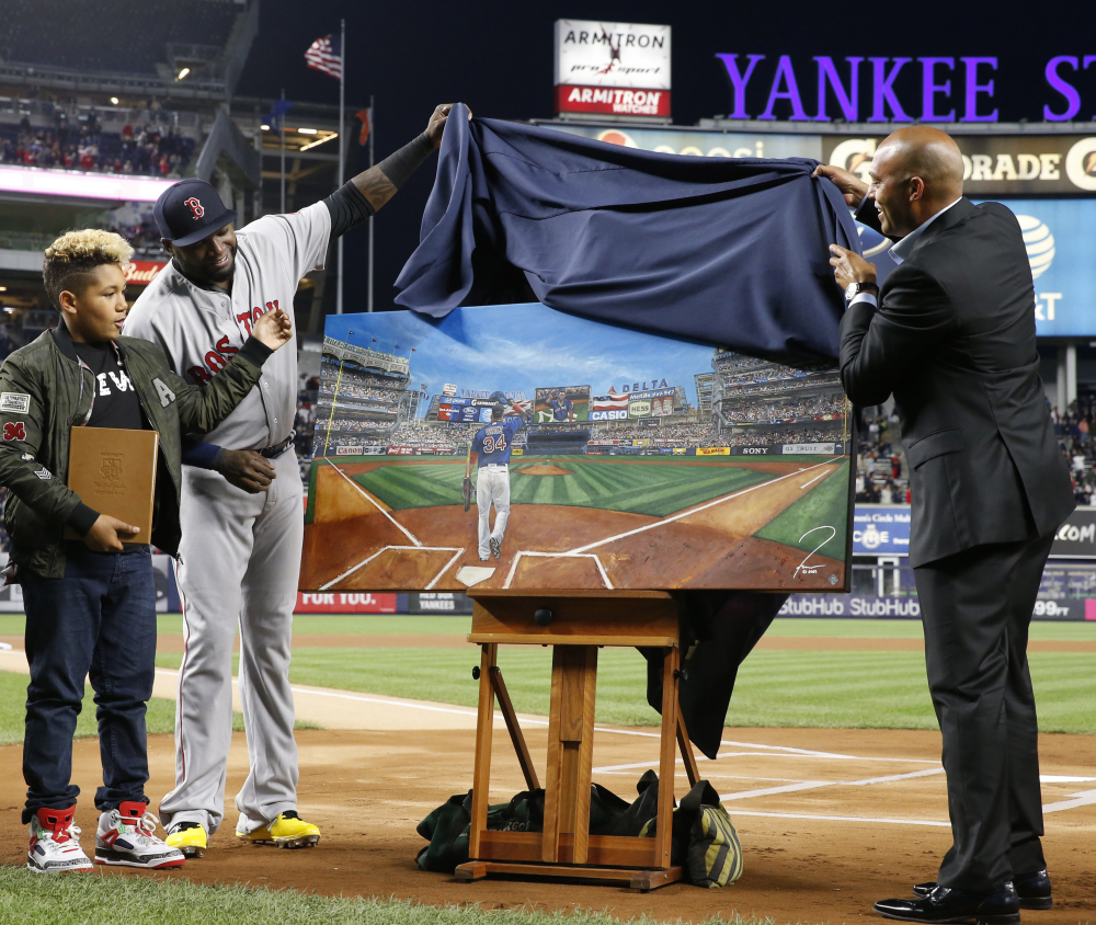 Boston Red Sox designated hitter David Ortiz, second from left, and his son D'Angelo, left, watch as retired New York Yankees relief pitcher Mariano Rivera helps unveil a painting that was given to Ortiz by the Yankees on Thursday in New York.