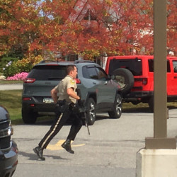 A Kennebec County sheriff's deputy runs across the driveway of the Camden National Bank in Manchester on Friday as police look for a bank robbery suspect.