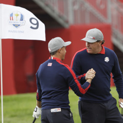 Phil Mickelson celebrates with teammate Rickie Fowler after Fowler chipped in on the ninth to win the hole during a Ryder Cup foresomes match Friday at Hazeltine National Golf Club in Chaska, Minnesota.
