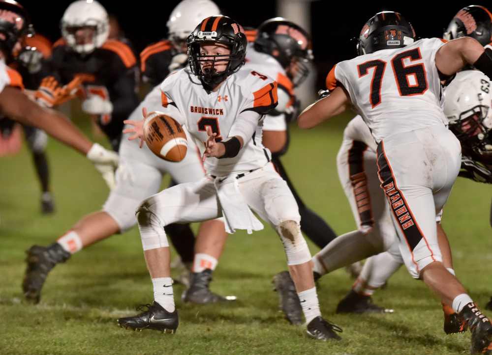 Brunswick quarterback Christian Jensen pitches the ball to Hunter Garrett during a Pine Tree Conference Class B game Friday night in Skowhegan.