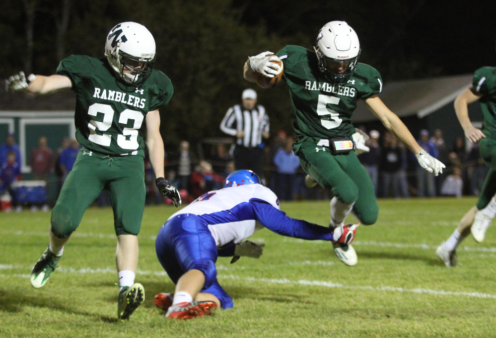 Winthrop/Monmouth's Nate Scott gets tripped up by Oak Hill High School's Austin Noble as Dylan Boynton (23) looks on during first-half action on Friday night in Winthrop.