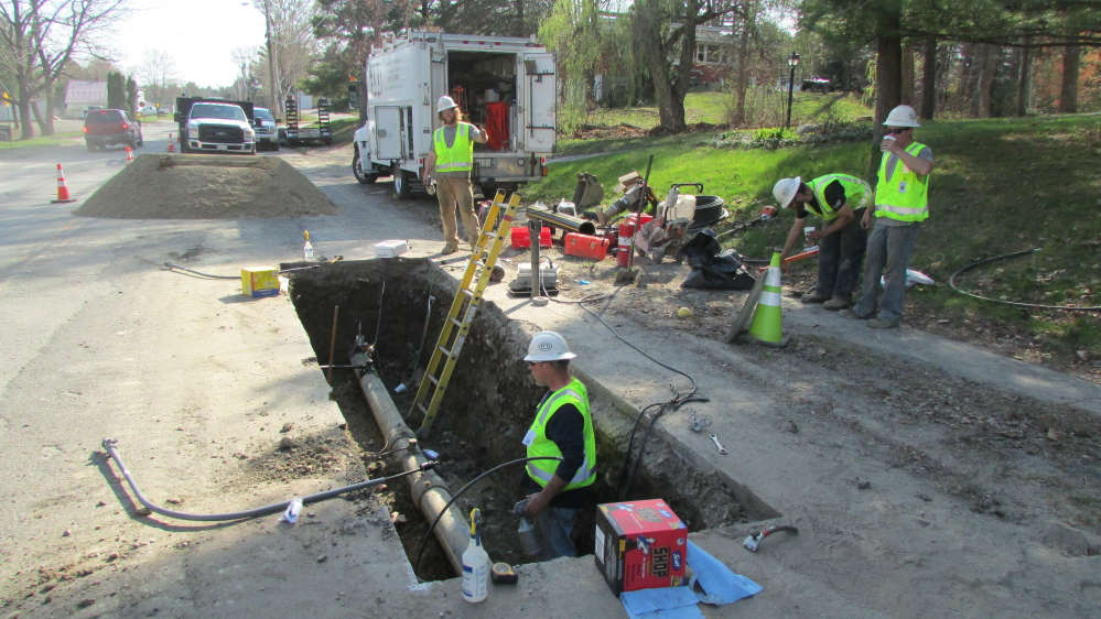 Employees of ETTI, a utilities construction company from Lisbon Falls, work on a Summit Natural Gas line in April in Waterville. Summit has been ordered by state regulators to inspect hundreds additional pipeline connections that may be faulty.