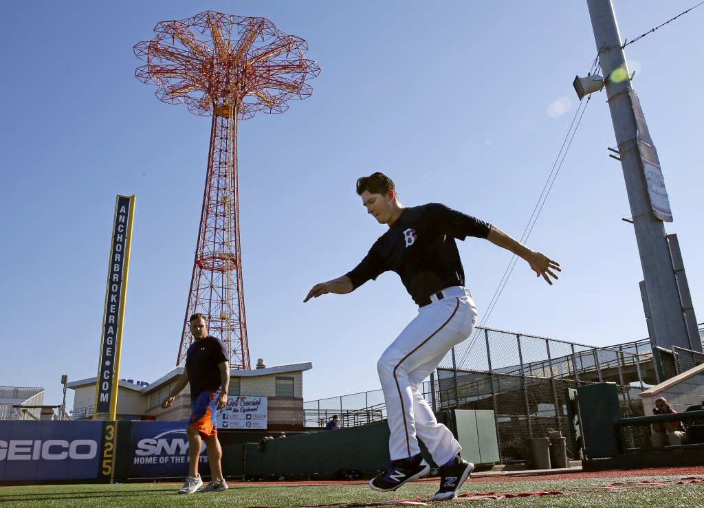 Brooklyn Cyclones strength coach Joe Lego watches pitcher Gary Cornish perform agility drills in the shadow of Coney Island amusement park.  Known for long bus rides between often picturesque ballparks, the minor leagues are hamlets of hope populated by a few bonus babies and thousands of conventional kids trying to grind their way up the pecking order to the sport's highest level.    Associated Press/Kathy Willens