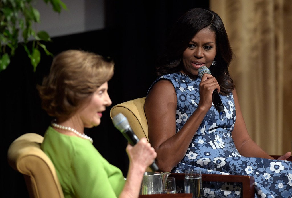 """First lady Michelle Obama and former first lady Laura Bush speak during the """"America's First Ladies: In Service to Our Nation"""" conference at the National Archives in Washington on Friday."""