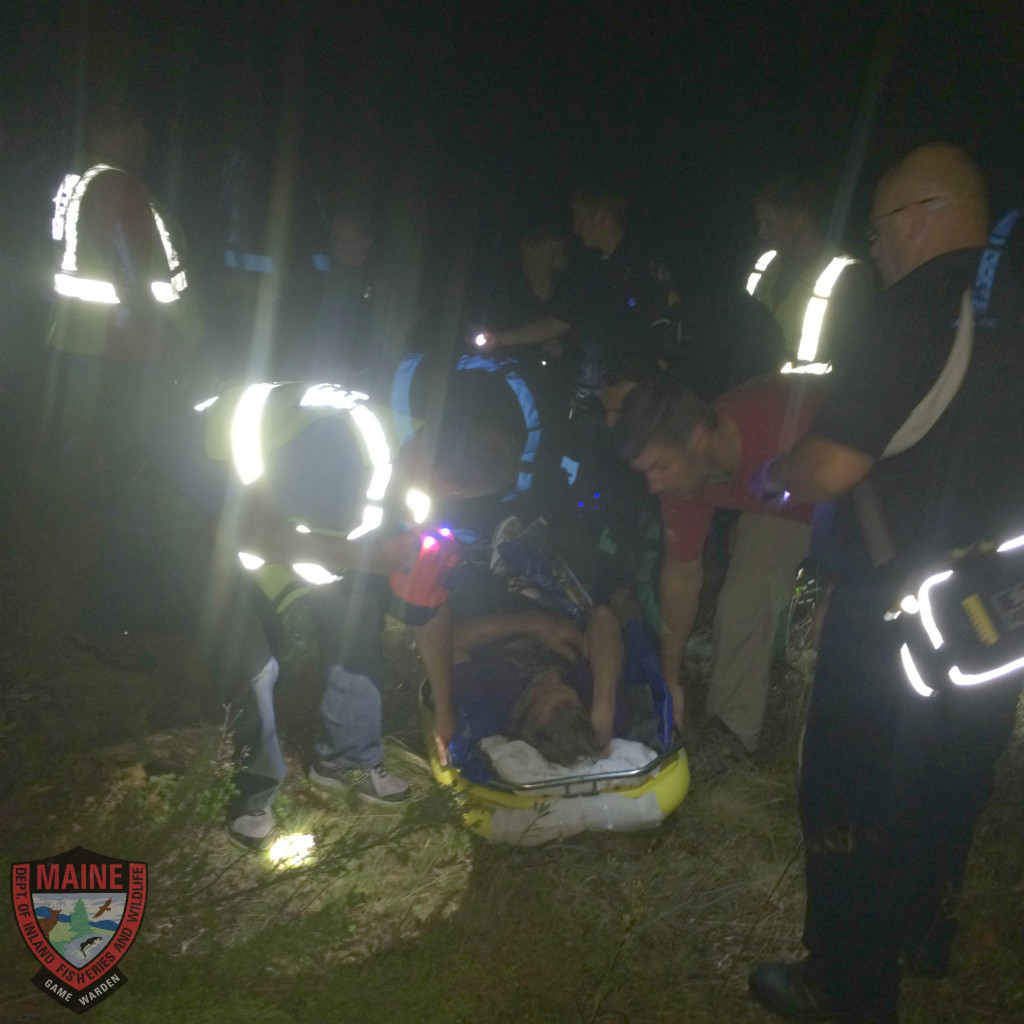 Rescuers tend to an old man with dementia who got lost in the woods in Camden on Tuesday night. (Courtesy Maine Game Wardens)