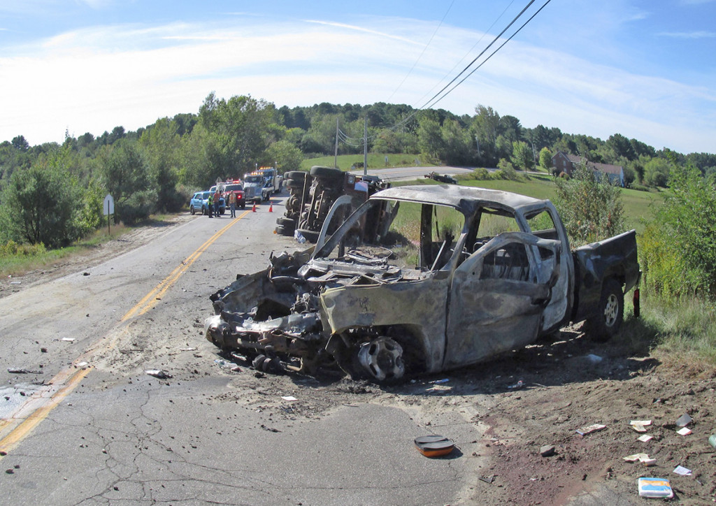 The pickup caught fire after colliding with the dump truck and passers-by pulled three men from the burning truck. Two of the occupants died and one is in critical condition. <em>Photo courtesy of the Maine Department of Public Safety</em>