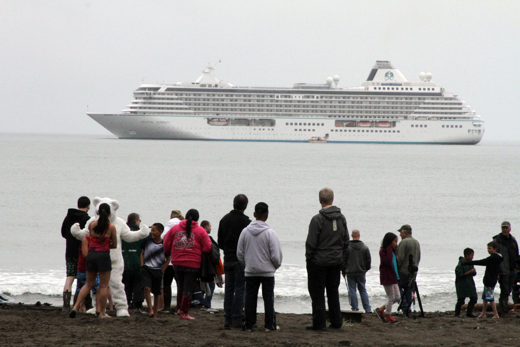 People prepare to take a polar plunge in the Bering Sea as the luxury cruise ship Crystal Serenity lies anchored offshore in Nome, Alaska, on Aug. 21. <em>Mark Thiessen/Associated Press</em>