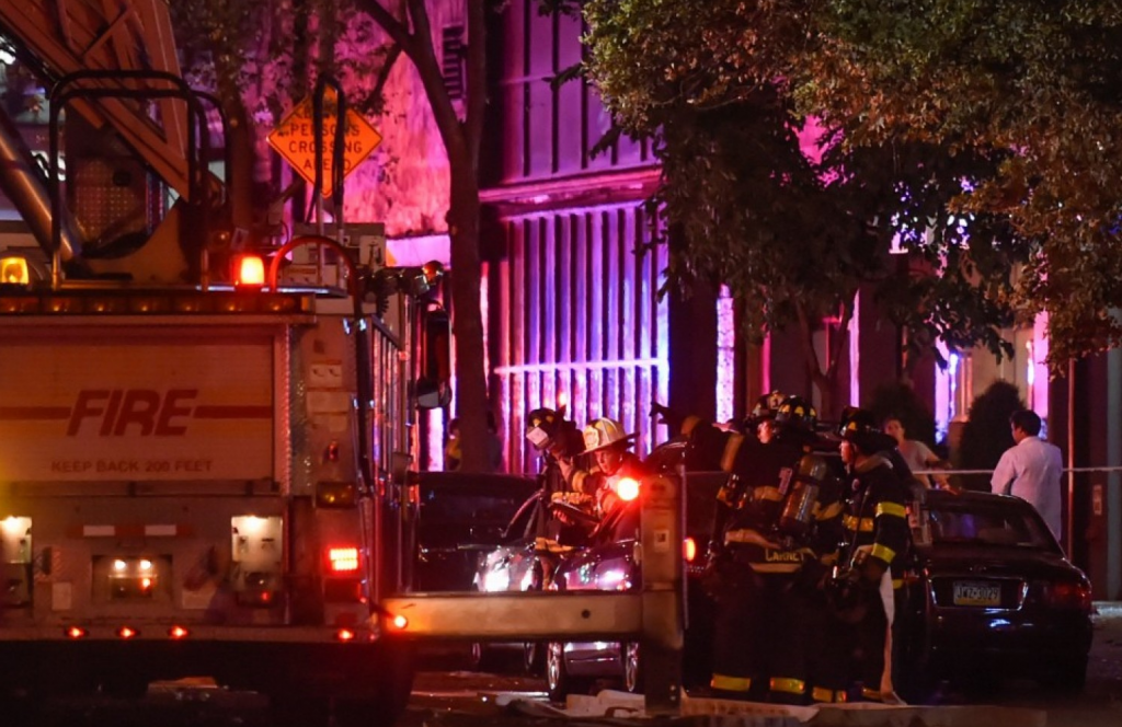 New York City firefighters stand near the site of an explosion in the Chelsea neighborhood of Manhattan on Saturday night. Rashid Umar Abbasi/Reuters