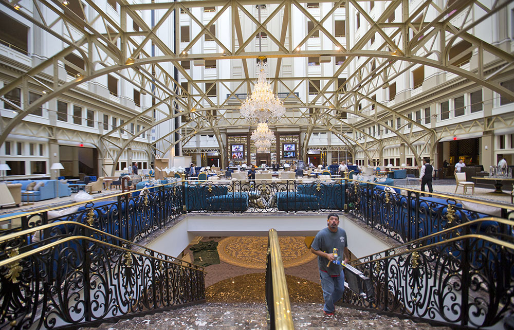 """Workers apply finishing touches to the grand concourse of Trump International Hotel during its """"soft opening"""" in downtown Washington in early September."""