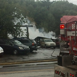Firefighters work to extinguish a fire at Hanson Auto on Route 4 in Turner on Friday.