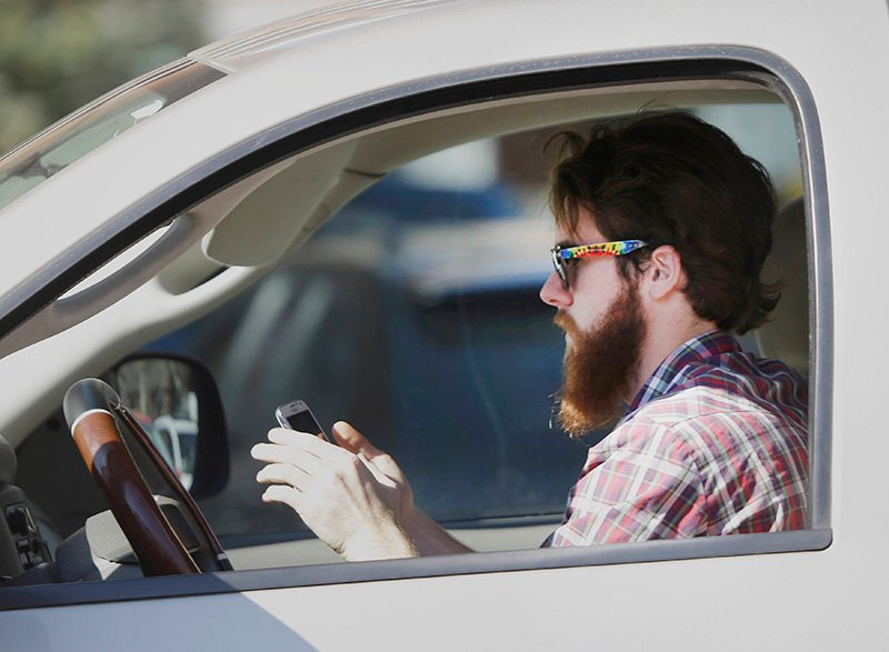 FILE - In this Feb. 26, 2013 file photo, a man uses his cell phone as he drives through traffic in Dallas. In a new survey, 98 percent of motorists who own cellphones and text regularly were aware of the dangers, yet three-quarters of them admit to texting while driving, despite laws against it in some states. Two-thirds said they have read text messages while stopped at a red light or stop sign, while more than a quarter said they have sent texts while driving. (AP Photo/LM Otero)