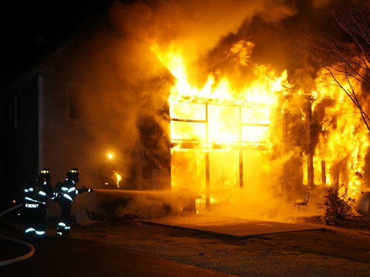 An apartment building at 54 Beal St. in Norway is engulfed in flames Monday night.  <em>Photo courtesy of WCSH</em>
