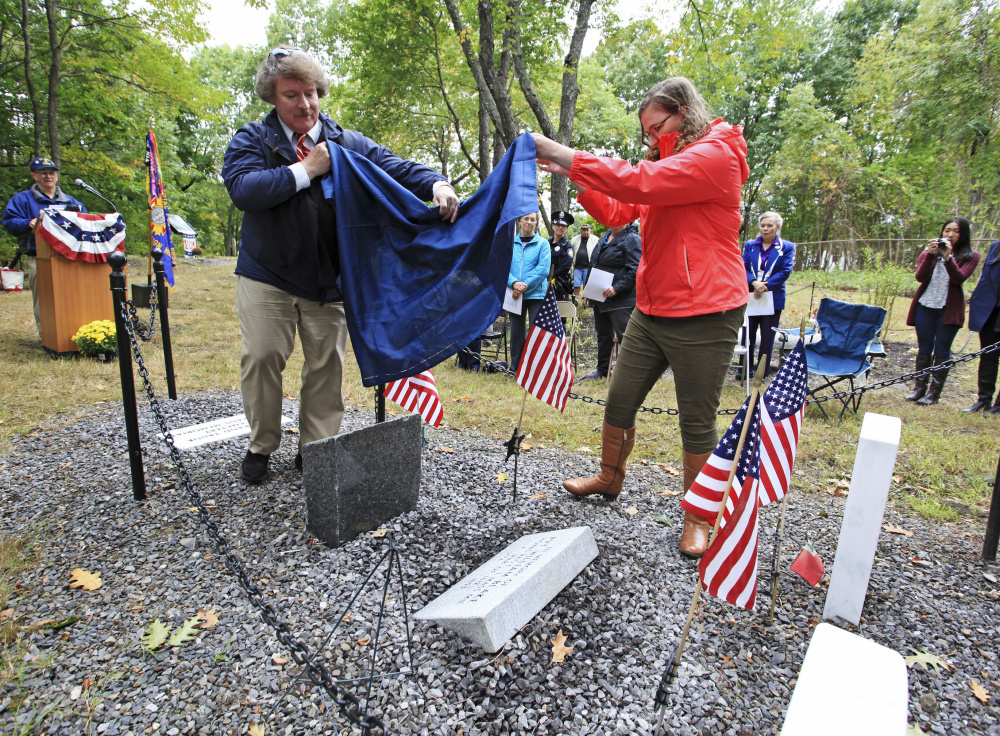 Herbert Adams and Samantha Allshouse unveil a grave marker in memory of William Blake at Grand Trunk Cemetery in Portland on Sunday. Blake was a private in the militia of a Massachusetts regiment called up to defend the port of Portland from the British in September 1814.
