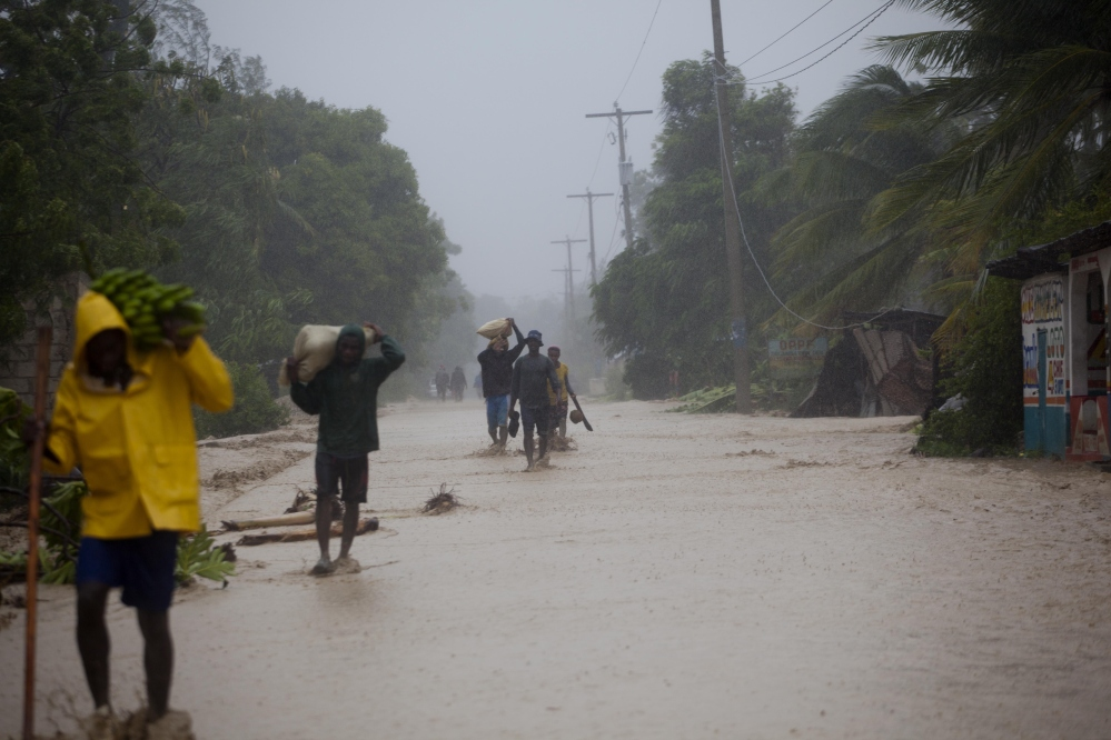 Residents walk in flooded streets as they return to their homes in Leogane, Haiti, on Tuesday. Hurricane Matthew slammed into Haiti's southwestern tip with 145 mph winds, tearing off roofs in the poor and largely rural area.
