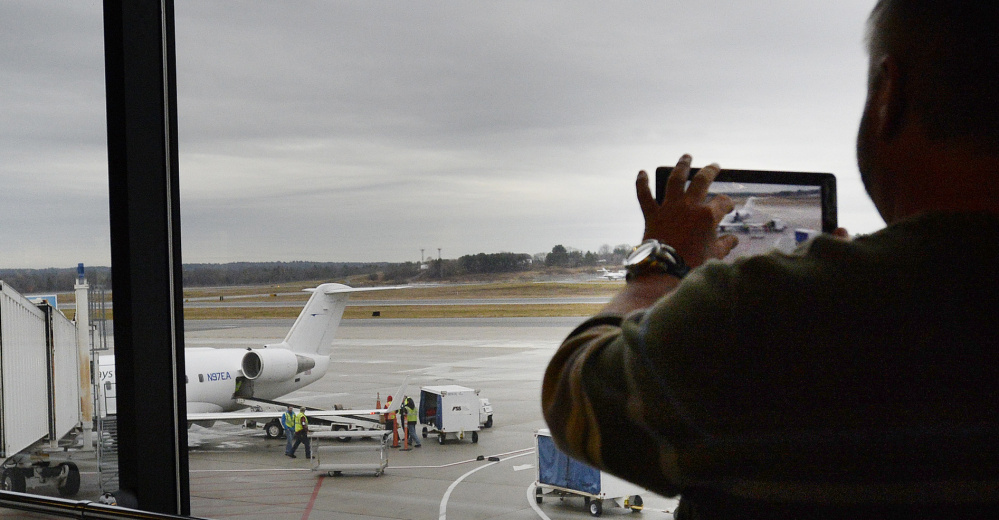A passenger photographs an Elite Airways plane at Portland International Jetport last fall. As Hurricane Matthew heads toward the U.S., many flights to Florida are being canceled. Thursday, many flights