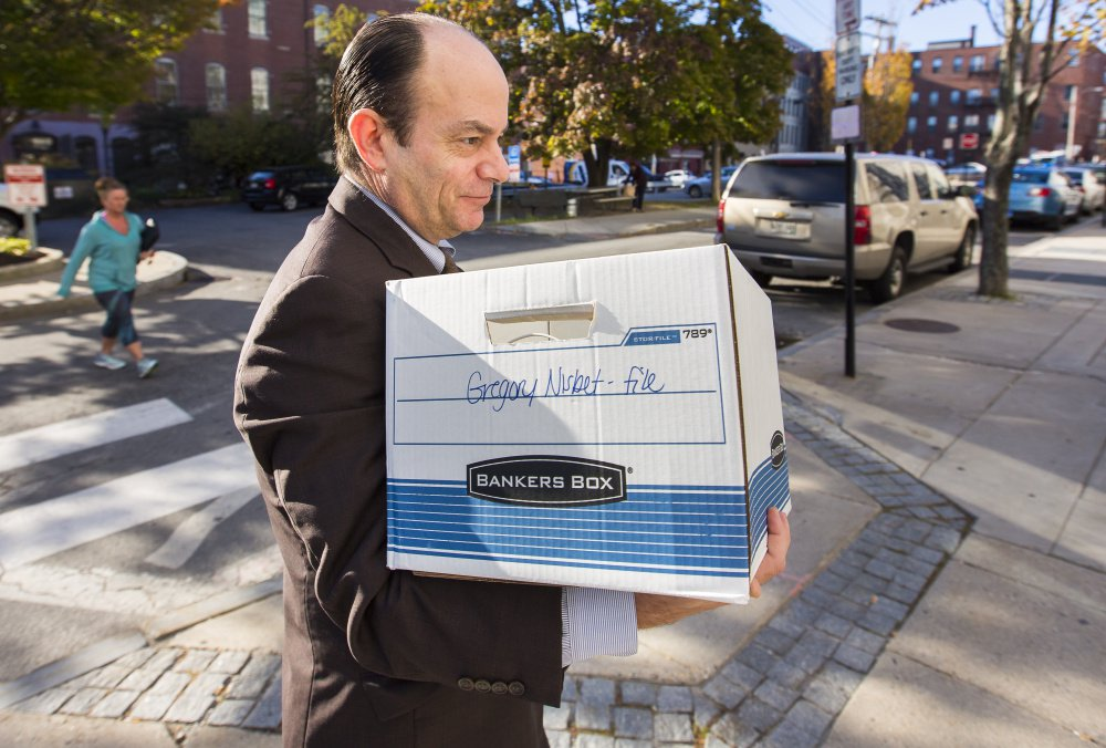 Matthew Nichols, defense attorney for landlord Gregory Nisbet, carries papers into the Cumberland County courthouse Wednesday. Nichols will start putting on his case Thursday.