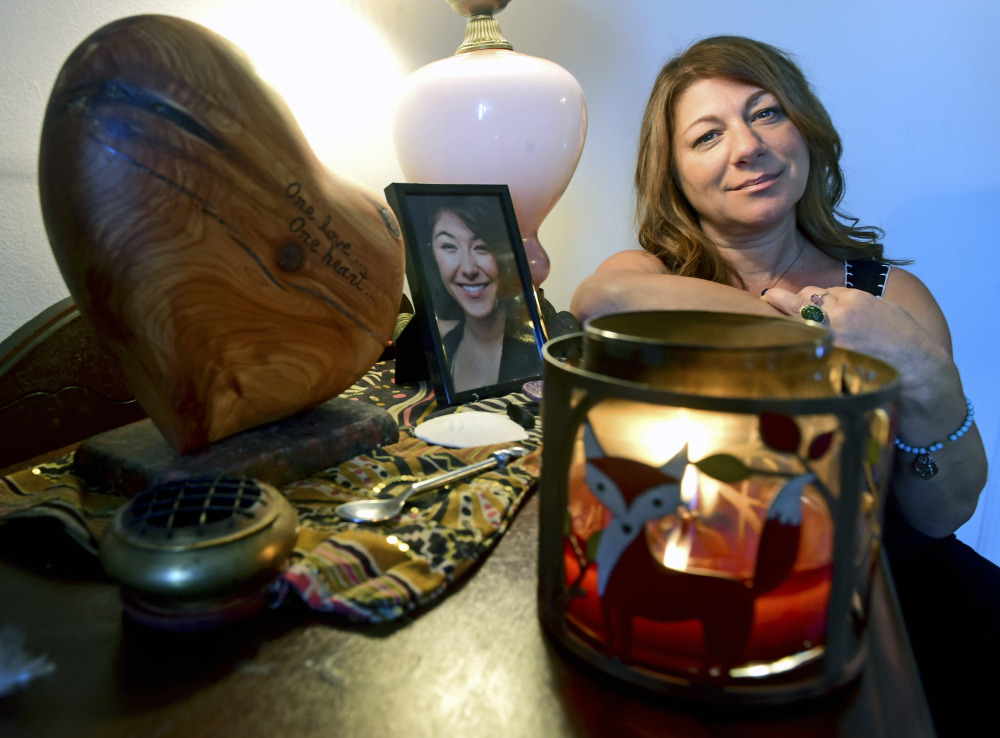 Donna Cimarelli, mother of murdered Maren Sanchez, sits next to a small memorial for her daughter that includes a heart shaped urn that holds Maren's ashes in her home in Milford, Conn. Maren Sanchez was killed by a high school classmate in April 2014.