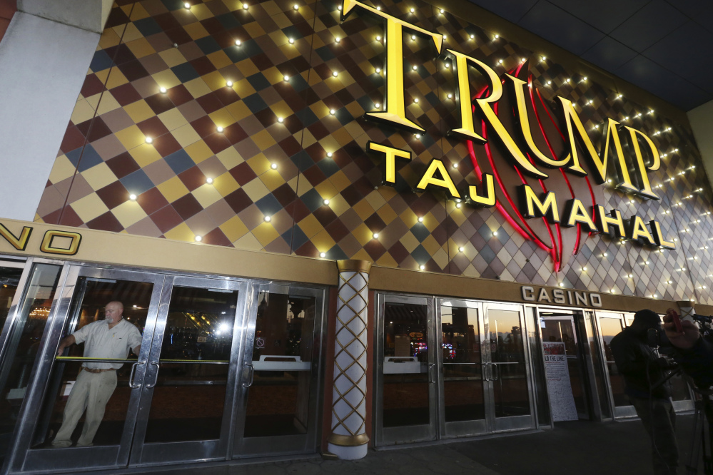 A worker measures the doorway to block the entrance at the Trump Taj Mahal on Monday in Atlantic City, N.J. The sprawling Boardwalk casino, with its soaring domes, minarets and towers built to mimic the famed Indian palace, shut down at 5:59 a.m., having failed to reach a deal with its union workers to restore health care and pension benefits that were taken away from them in bankruptcy court.