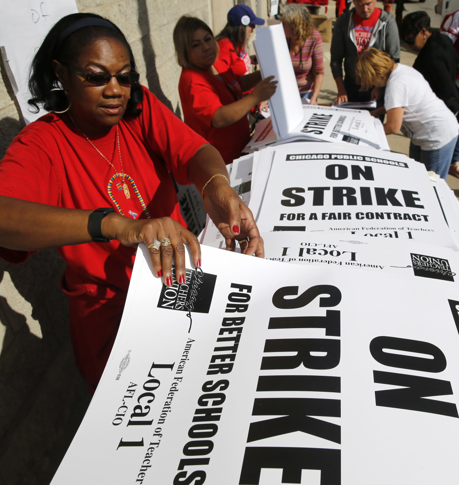 Retired Chicago school teacher Patricia Lofton counts through a stack of picket sign for Chicago Teachers Union members to pick up Monday in Chicago.