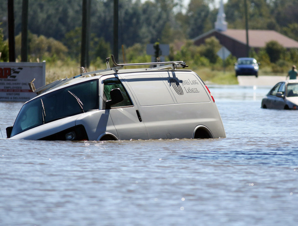 Abandoned vehicles sit in floodwaters Monday in Goldsboro, N.C., where the waters are expected to rise through Tuesday morning and persist all week.