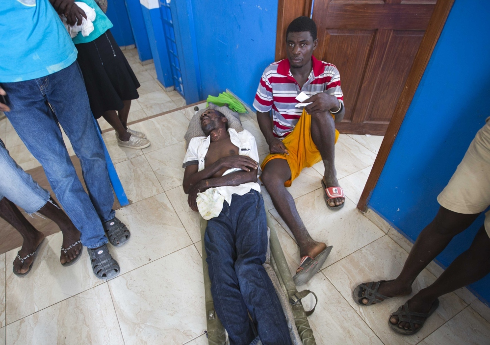 A man lies on a litter at a police station Monday that is serving as a makeshift clinic for cholera patients and people injured by Hurricane Matthew, in Marfranc, Haiti.